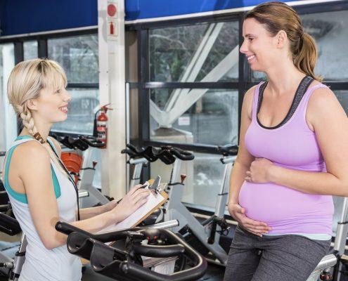 Gravis kvinne på trimsykkel med trener