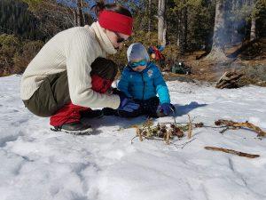 Kvinne tenner bål i skogen med liten sønn