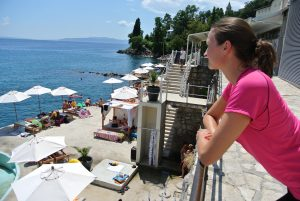 Ung kvinne på strandpromenade ser utover havet