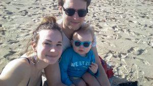 Ung familie sitter på en strand