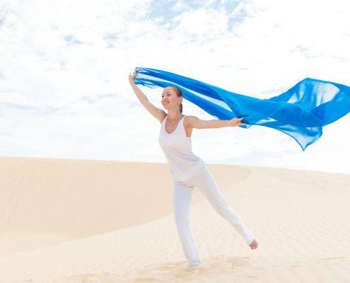 Kvinne strand blått sjal flyr i vinden