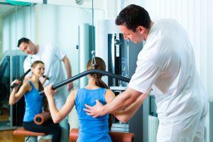 Fysioterapeut veileder pasient som trener