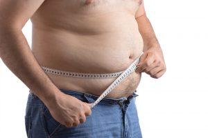 Mann med målebånd rundt magen