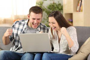 Ungt par jubler foran en laptop