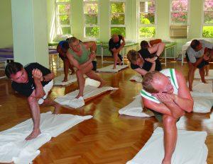 Mennesker i treningstøy står i en tøyeposisjon i gymsal