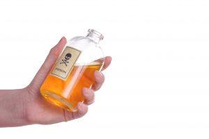 Flaske med gult innhold og giftlogo