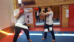 Mann trener ungdom med boksehansker