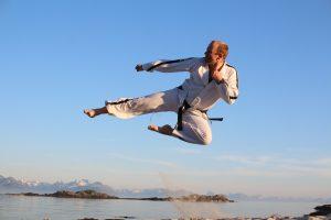 Mann med kampsporthopp i idylliske strandomgivelser