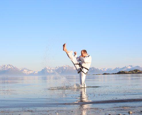 Mann står i sjøen og gjør høyt Taekwon-Do-spark