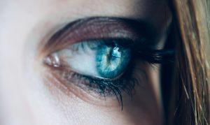 Nærbilde av kvinnes øye hvor et vindu speiles i det