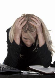 Person me dlangt lyst hår sitter med hodet i hendene over en pult med data og kontorrekvisita