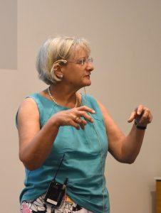 Eldre dama holder holder krokete fingre foran seg mens hun snakker