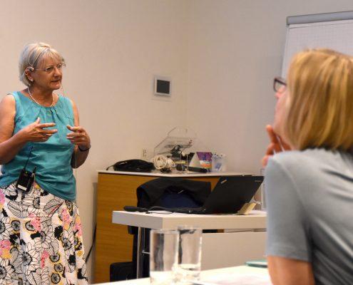 Eldre dame holder foredrag, en tilhører er uskrap