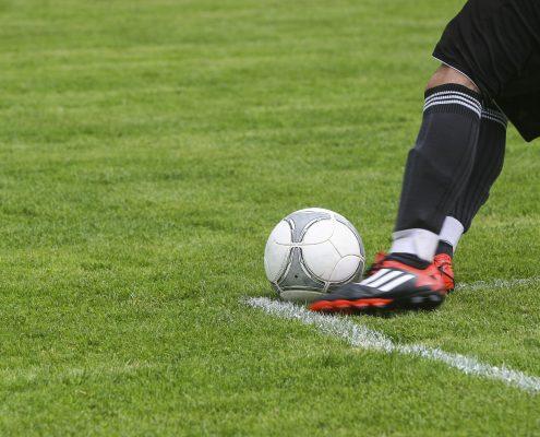 Kun bena til en fotballspiller mot en ball