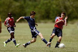 Tre unge gutter i fotballdrakter kjemper om en ball