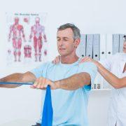 Kvinnelig fysioterapeut veileder mann som trener med strikk