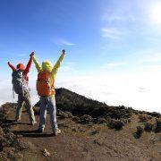 To tyrkledde jubler med armene i været på en fjelltopp