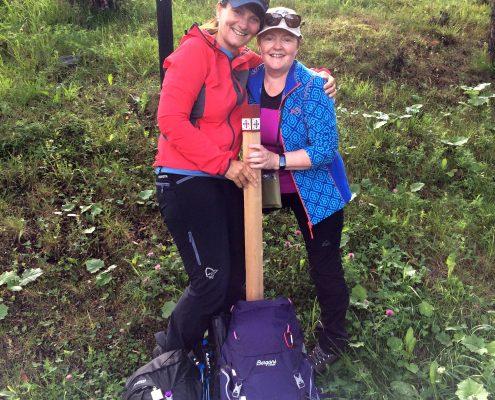 To kvinner i turtøy med et pilegrimsledemerke mellom seg og sekkene på bakken