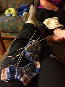 To par kvinnebein i sofa med strikketøy i fanget