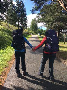 To kvinner med tursekker bakfra som leier hverandre mens de vandrer