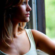 Ung kvinne ser trist ut av vinduet