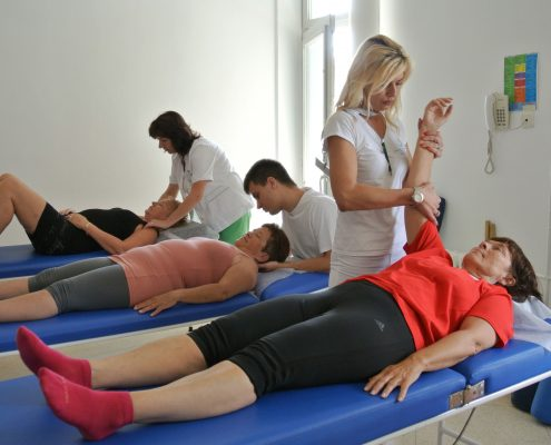 Kvinne ligger på terapibenk i Opatija mens fysioterapeut beveger armen