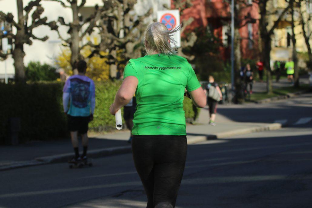 Kvinne løper med grønn t-trøye