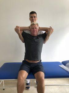 Fysioterapeut drar armene til en mann bakover