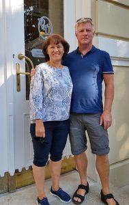 Par i helfigur står utenfor døren til hotellet