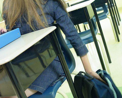 Ung kvinne ved pult bøyer seg ned mot ranselen på gulvet