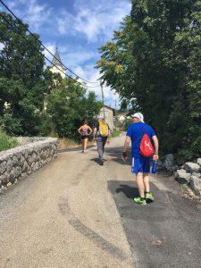 Tre personer i turtøy på vei opp bakker i en fjelllandsby