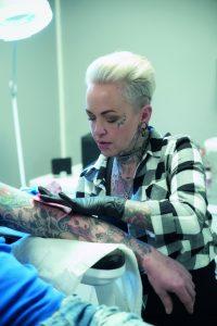 Kvinnlig tatovør tatoverer en arm på en kunde