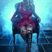 Kvinne i rød sexy kjole med mange tatoveringer sitter i en gammeldags stol omringet av røyk