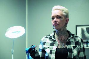 Kvinnlig tatovør med tatoveringsutstyr i hånden