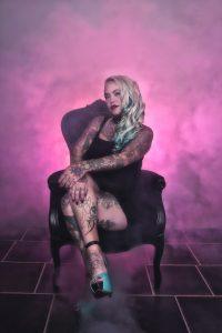Kvinne med kroppen full av tatoveringer sittende i en stol omringet av røyk