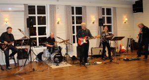 Fem bandmedlemmer spiller i en festsal