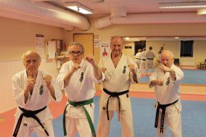 Fire eldre menn i karatedrakter