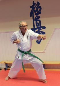 Eldre mann i karatedrakt og karateposisjon