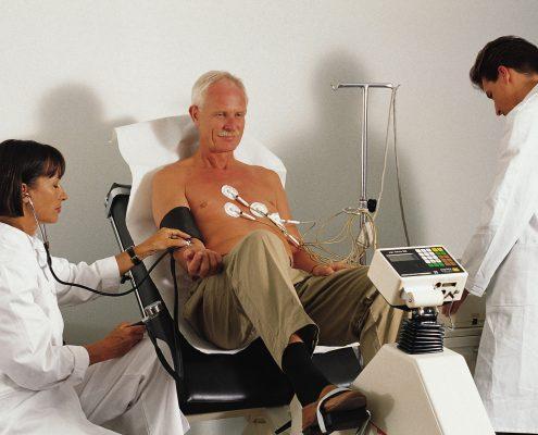 Mann får målt blodtrykk og tester hjertet