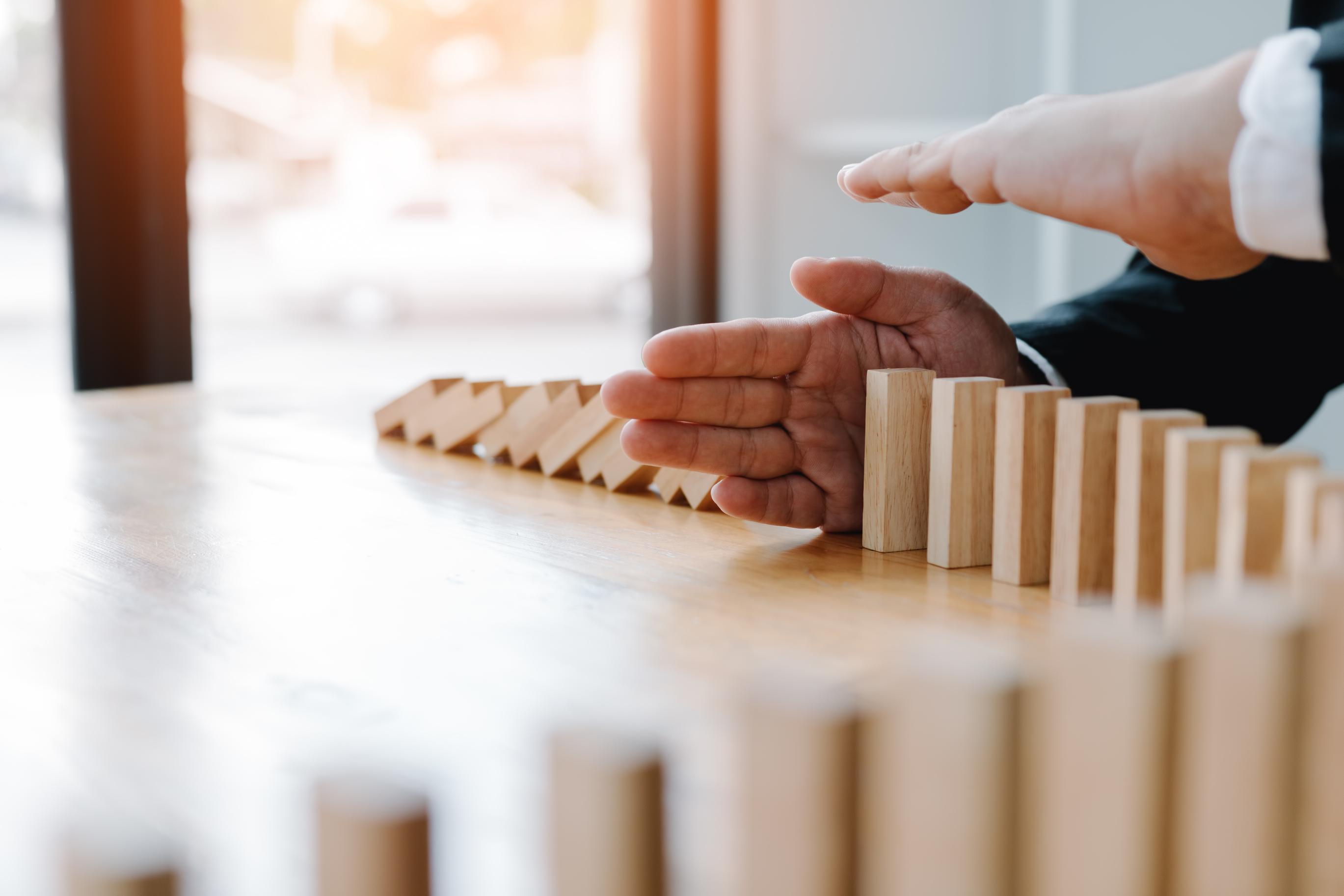 Manns hender stopper dominobrikker fra å ramle
