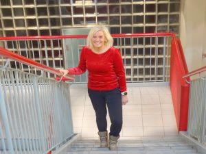 Kvinne går smilende opp en trapp