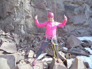 Kvinne i rosa klatreutstyr viser to tomler opp