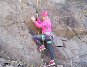 Kvinne med rosa hjelm i steinbrudd i ferd med å klatre