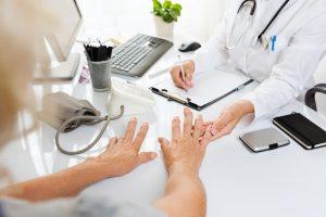 Lege undersøker pasient med artritthender
