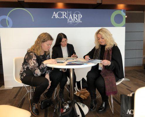 Tre kvinner studerer programmet fra forskningskonferanse