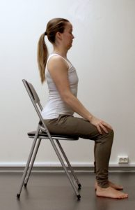 Kvinne sitter på stol og trekker brystkassen litt frem og opp