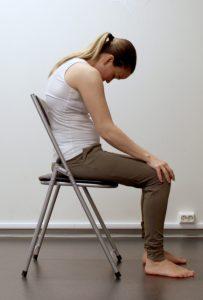 Kvinne sitter på stol og ruller hodet og skulderparti framover