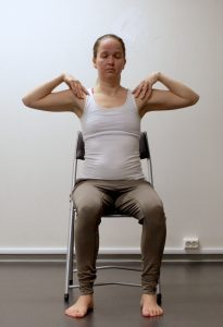 Kvinne sitter på stol med hendene på skuldrene og ansiktet rett fram