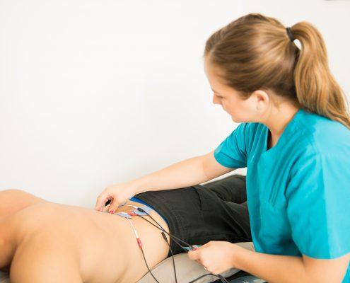 Fysioterapeut setter elektroder på ryggen til en pasient