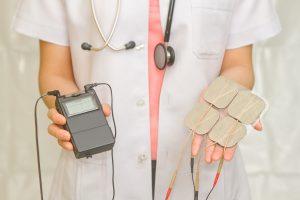 Lege holder fram TENS-apparat og elektroder